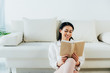cheerful latin woman reading book while sitting on floor near couch