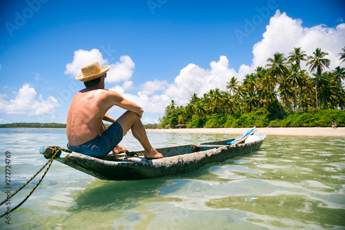 Tourist wearing a straw sun hat sitting in a rustic dugout canoe on a sunny palm Canvas Print