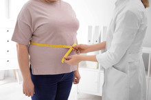 Doctor Measuring Waist Of Overweight Woman In Clinic, Closeup