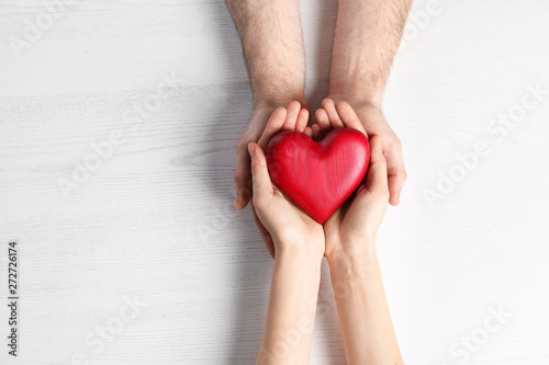Couple holding decorative heart on white wooden background, top view - 272726174