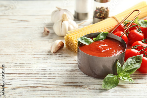 Fotomural  Pan of tasty tomato sauce served on wooden table. Space for text