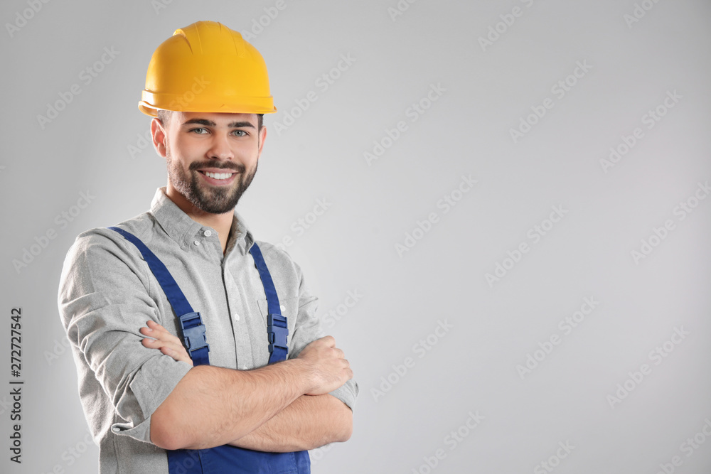 Fototapeta Portrait of professional construction worker in uniform on grey background, space for text