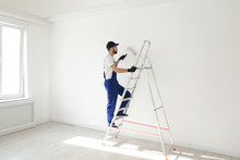 Handyman Painting Wall With Roller Brush Indoors. Professional Construction Tools