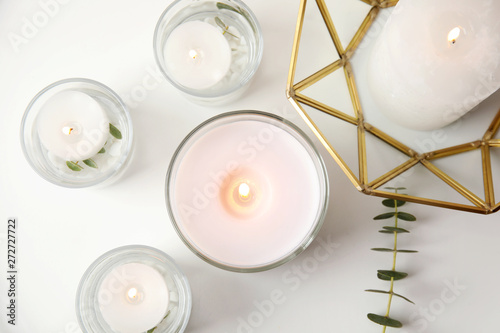 Fototapeta  Flat lay composition with burning aromatic candles and eucalyptus on white table
