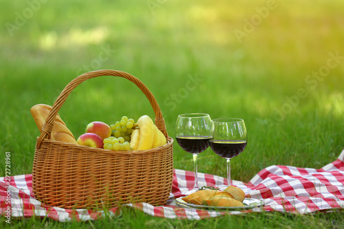 Stickers pour portes Pique-nique Wicker basket with food and wine on blanket in park, space for text. Summer picnic