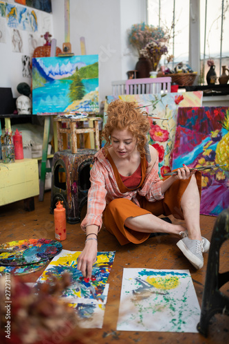 Poster Imagination Red-haired woman wearing orange trousers coloring on floor