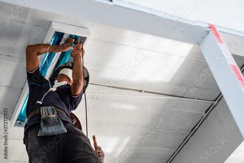 Technician is installing fluorescent bulbs on ceiling of building Wallpaper Mural