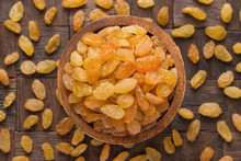 Golden Raisins In Wooden Bowl, Top View.
