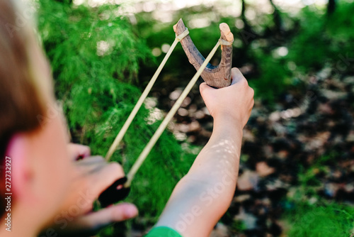 Leinwand Poster Boy enjoying his summer vacation throwing rocks with a slingshot in a forest