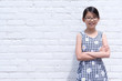 Portrait of young Asian girl teen wearing eyeglasses against white brick wall