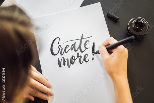 Obraz Creat more. Calligrapher Young Woman writes phrase on white paper. Inscribing ornamental decorated letters. Calligraphy, graphic design, lettering, handwriting, creation concept - fototapety do salonu