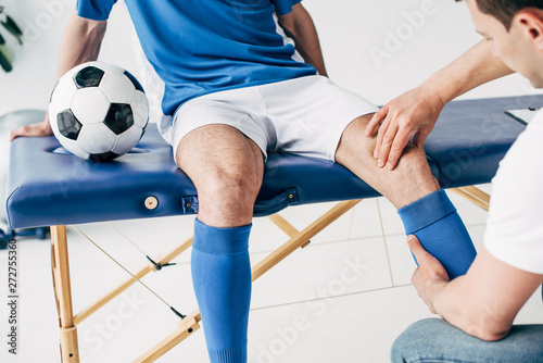 partial view of Physiotherapist massaging leg of football player in hospital - 272755360