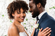 canvas print picture - cheerful african american bride hugging handsome bridegroom near flowers