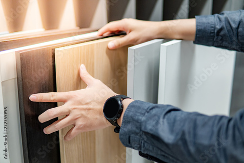 Obraz Male hand choosing cabinet panel materials or countertops for built-in furniture design. Shopping furniture and decoration. Home improvement concept - fototapety do salonu
