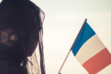 Muslim Woman In Scarf With French Flag Of At Sunset.Concept
