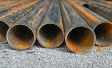 Rusted Construction Pipe Laid On Asphalt