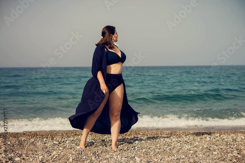 Fotografia Attractive busty curvy woman in a blue swimsuit resting on the beach