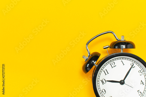 Obraz Black retro alarm clock on yellow background top view Flat lay copy space. Minimalistic background, concept of time, deadline, time to work, morning - fototapety do salonu