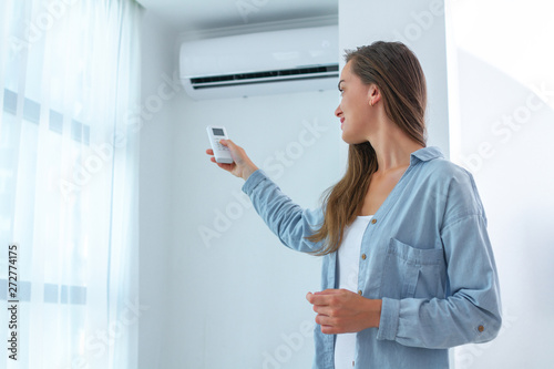 Young woman adjusts the temperature of the air conditioner using the remote cont Wallpaper Mural