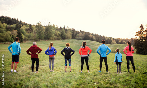 Rear view of large group of multi generation sport people standing in nature.