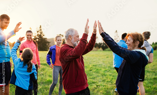Fototapeta Large group of fit and active people resting after doing exercise in nature. obraz