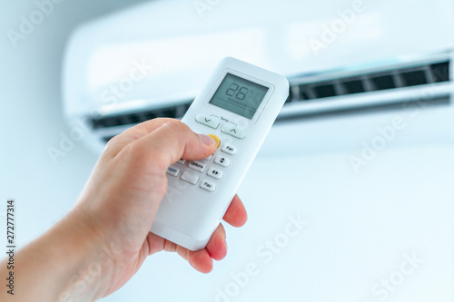 Photo Air conditioner temperature adjustment with remote controller in room at home