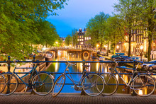 Old Bicycles On The Bridge In Amsterdam, Netherlands Against A Canal During Summer Twilight Sunset. Amsterdam Postcard Iconic View. Tourism Concept.