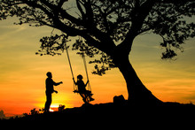 The Silhouette Of Tourists Playing Swings With Big Trees, Couples And Swings During The Sunset, Concept Travel With Nature.