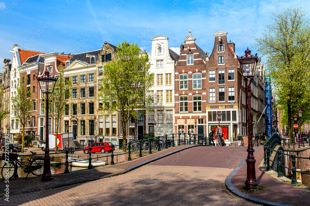 Traditional dutch old houses and bridge in Amsterdam, Netherlands. Summer sunny day