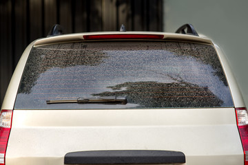 rear view of a dirty car, hatchback with a dusty trunk lid and a faulty car wiper.