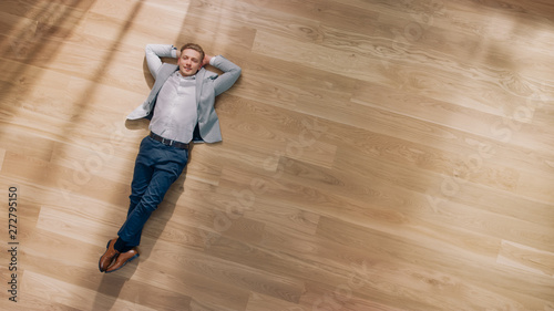 Photo sur Aluminium Akt Young Man is Lying on a Wooden Flooring in an Apartment. He's Wearing a Jacket and White Shirt. Cozy Living Room with Modern Minimalistic Interior and Wooden Parquet. Top View Camera Shot.