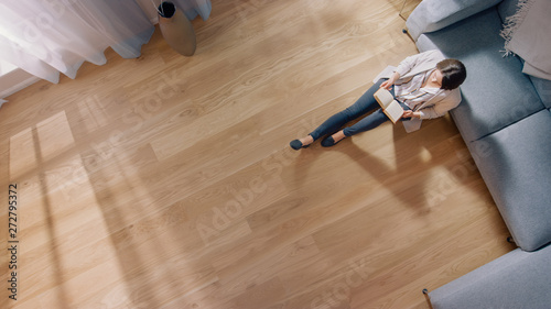 Fotografia Young Woman is Sitting on a Floor and Reading a Book