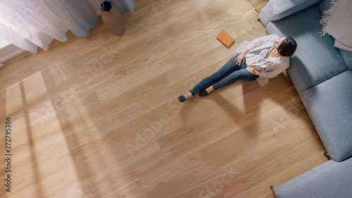 Fotomural Young Woman is Sitting on a Floor and Looking out of the Window after Reading a Book