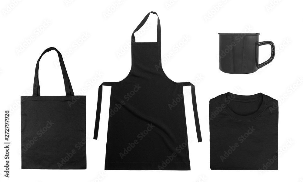 Fototapeta Collection of black objects isolated on white background. Black cotton bag, black folded t-shirt, kitchen apron, metal mug. Flat lay. Top view