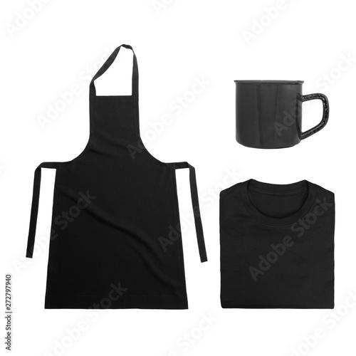 Fototapety, obrazy: Collection of black objects isolated on white background. Black blank apron, black folded t-shirt, metal mug. Flat lay of branding or identity mockup design.