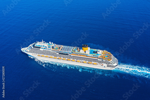 Aerial view of beautiful modern large white cruise ship liner with colorful deck against clear blue sea background. Top view from drone of floating liner