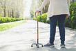 canvas print picture - Senior disabled caucasian woman hands on cane outside nursing home park. Close up of elderly lady holding a walking stick outdoors of healthcare facility on the sunny day.