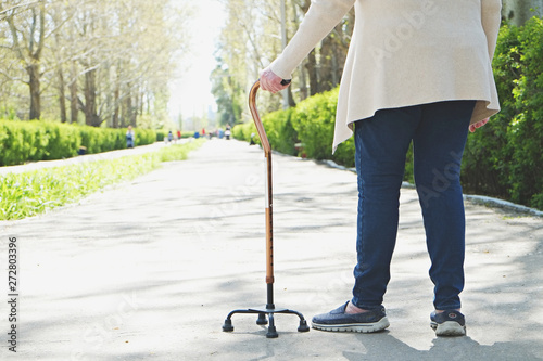 Fotografiet Senior disabled caucasian woman hands on cane outside nursing home park