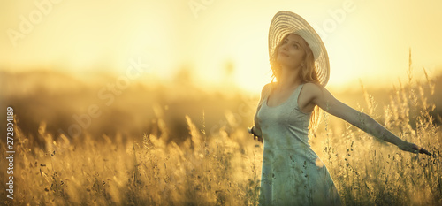 Happy young woman on the sunset or sunrise in summer nature with open hands