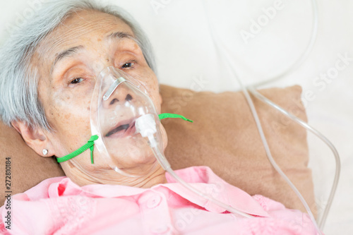 Closeup of female senior patient putting inhalation or oxygen mask in hospital b Fototapete
