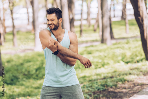 cheerful young sportsman smiling while stretching in sunny park