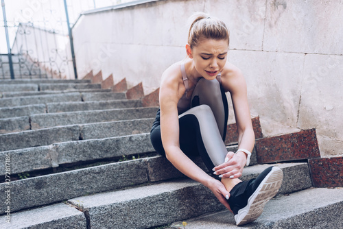 fototapeta na drzwi i meble attractive sportswoman sitting on stairs and suffering from pain while touching injured leg