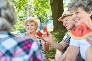 Gruppe Senioren im Park beim Melone essen