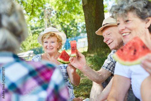fototapeta na lodówkę Gruppe Senioren im Park beim Melone essen