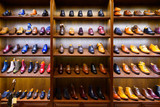 Fototapeta Uliczki - Full grain leather shoes on wooden display in men shoes boutique store. Black, brown and other colors.