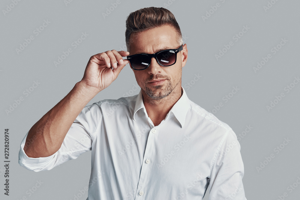 Fototapeta In his own style. Handsome young man looking at camera and adjusting sunglasses while standing against grey background