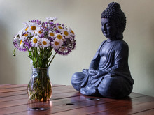 Calming Figurine Meditating Buddha And Jug With Lush Bouquet Stand On The Table