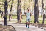handsome sportsman jogging along walkway in green sunny park
