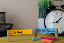 Seminar And Further Training. Handwriting On Sticky Notes In Clothes Pegs On Wooden Office Desk