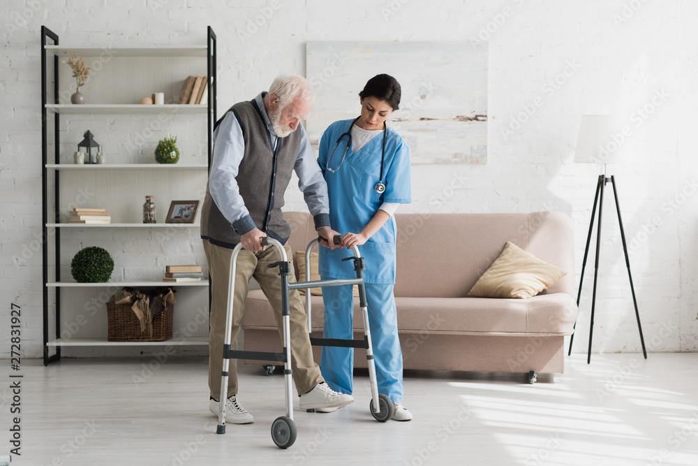 Fototapeta Nurse helping to senior man walking at home, recovering after injury